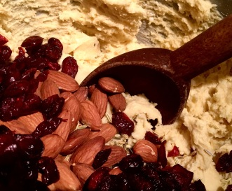 mixing-fennel-seeds-cranberries-and-almonds-into-the-batter-with-a-wooden-spoon