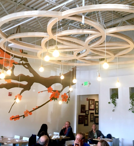 dining room, with wooden flower of life suspended from the ceiling